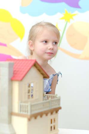 puppenhaus: Kleines M�dchen spielt mit Puppenhaus