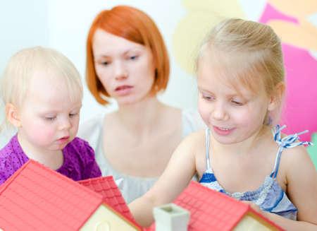 puppenhaus: Kinder und ihre Mutter spielt mit Puppenhaus
