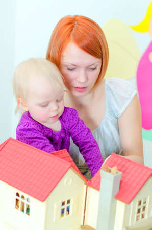 puppenhaus: Kind und seine Mutter spielt mit Puppenhaus