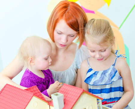 子供と母親のドールハウスで遊ぶ
