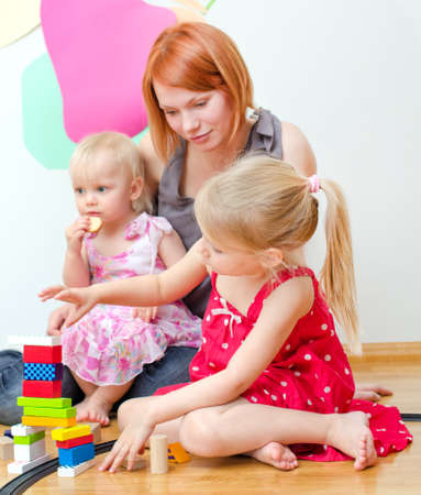 小さな女の子と彼女の母親は床に座って鉄道で遊んで