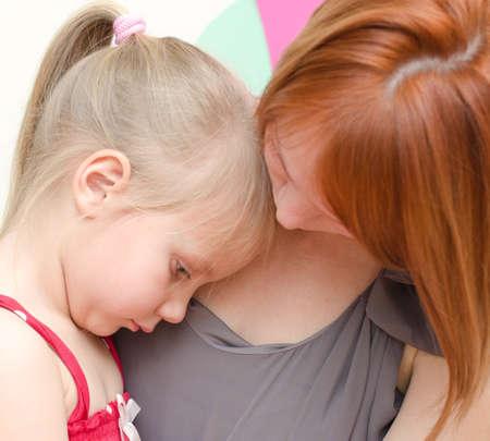 petite fille triste: M�re embrassant son enfant triste