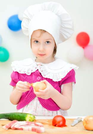 bacon portrait: Little girl in chief hat cooking dinner Stock Photo
