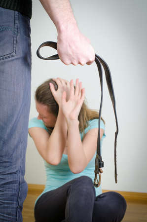 Man with belt coming to his wife. Home violence concept Stock Photo