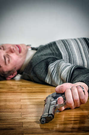 Man with gun laying on the floor photo