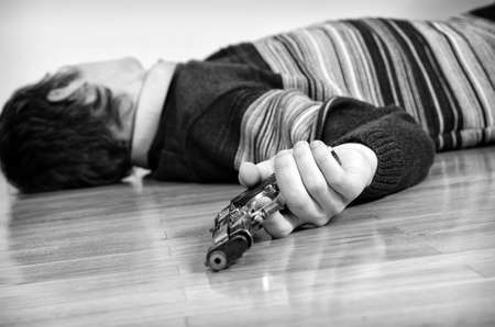Man with gun laying on the floor  Black and white photo