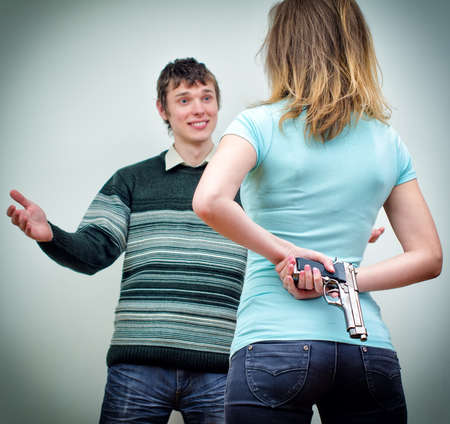 Woman hiding gun underhand talking to man photo