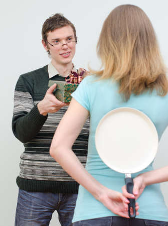 underhand: Woman hiding pan underhand talking to man