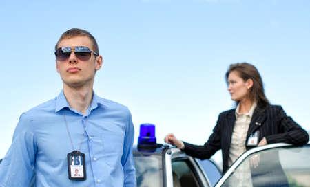 seguridad laboral: Dos agentes del FBI cerca el coche con luz intermitente
