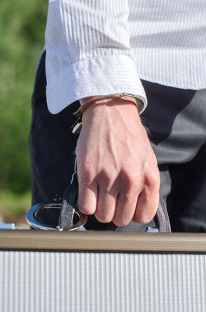Close up view of male hand enchained to suitcase photo