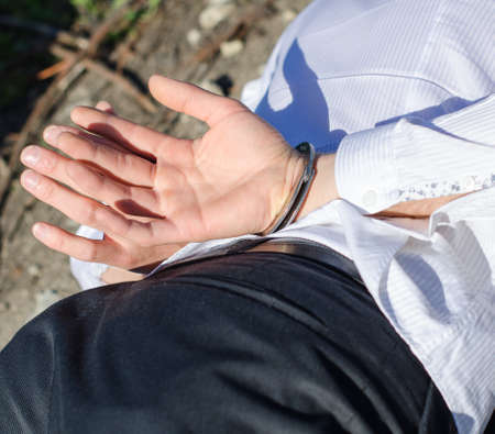 enchain: Close up view of male hands in handcuffs Stock Photo