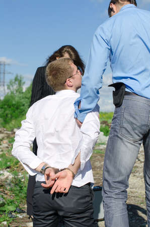 Two FBI agents conduct arrest of an offender photo