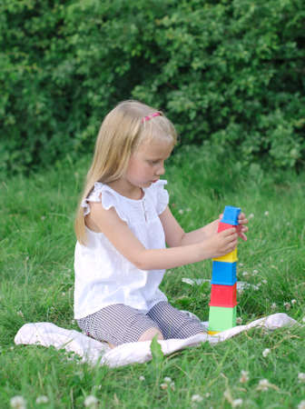 colored play: Little girl playing blocks in the park Stock Photo