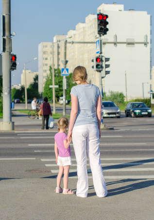 母と子が道路を横切って背面図 写真素材