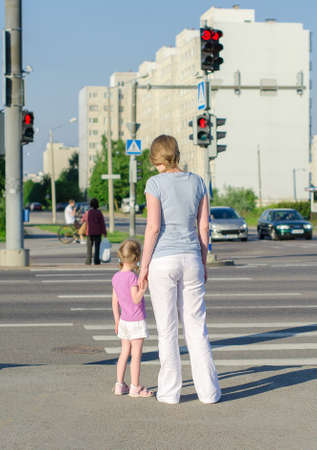 Mother and child crossing the road  Back view  Archivio Fotografico