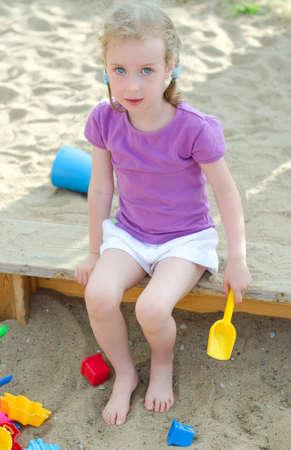 the sandbox: Little girl sitting near sandbox