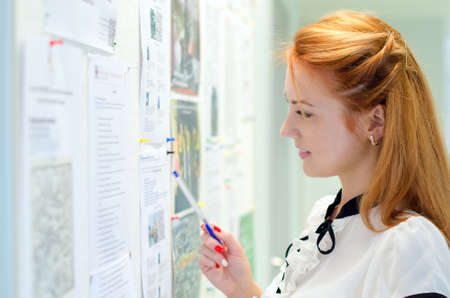 Young female student looking through job offers on board