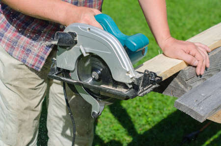 Handyman using hand-held saw machine outdoors photo