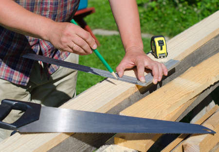 Male hands measuring and marking wooden plank outdoors photo