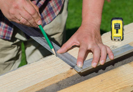 tradesperson: Male hands measuring and marking wooden plank outdoors