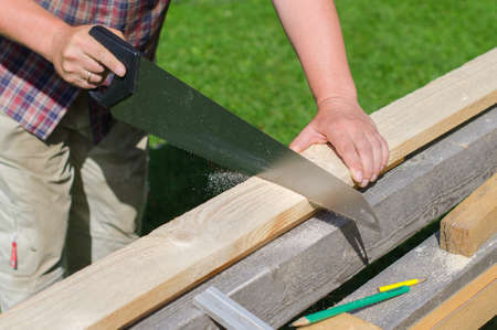 Handyman sawing long wooden plank outdoors photo