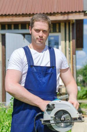 Handyman using hand-held saw machine outdoors photo