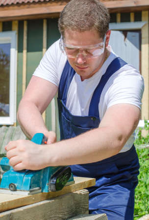 planer: Handyman using electric planer outdoors