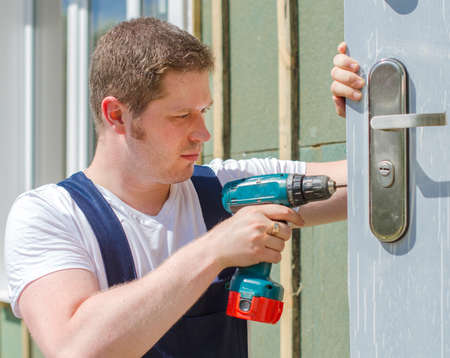 hand drill: Young handsome handyman using screwdriver