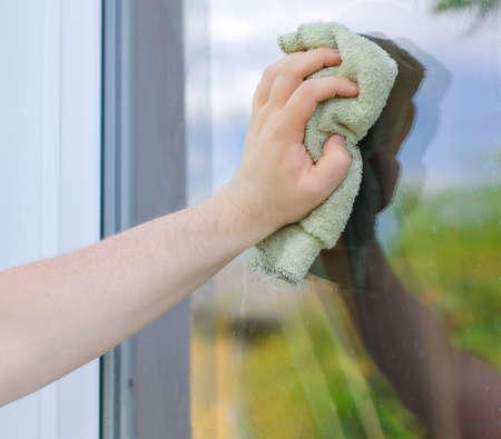 Male hand with rag washing window outdoors Stock Photo