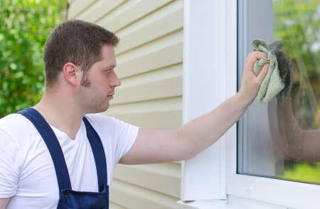 Homeworker with rag washing window outdoors photo