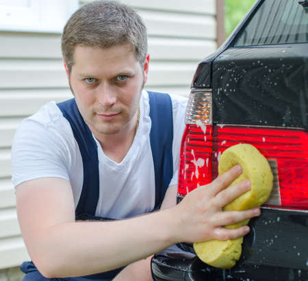 Young worker washing car with yellow sponge photo
