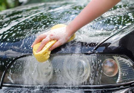 headlamp: Female hand with yellow sponge washing car Stock Photo