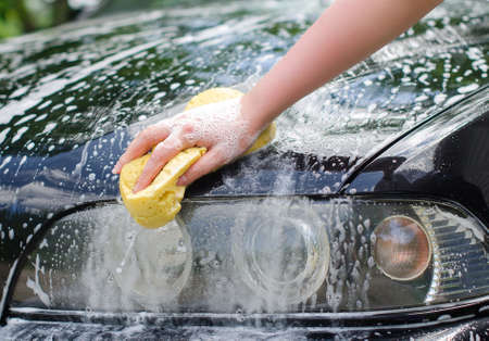 Female hand with yellow sponge washing car Archivio Fotografico