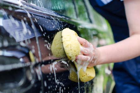 autolavaggio: Mano femminile con il giallo spugna lavaggio auto