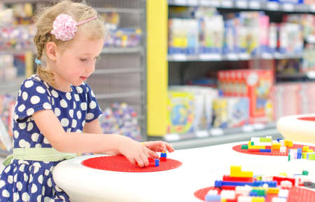Cute little girl playing with blocks in supermarket photo
