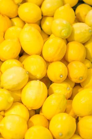 Lot of bright yellow lemons in supermarket