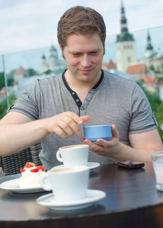 Young man have a rest with cup of coffee in outdoor cafe photo