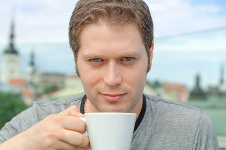 Handsome young man with cup of coffee photo