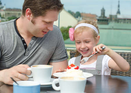 Father and daughter having lunch in outdoor cafe photo