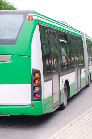 Modern green urban bus leaves from a stop photo