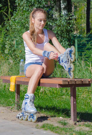 roller blade: Pretty girl sitting on the bench and putting on inline skates. Stock Photo