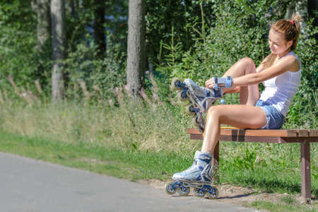 Pretty girl sitting on the bench and putting on inline skates. photo