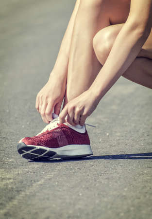 Woman tying laces before training 免版税图像