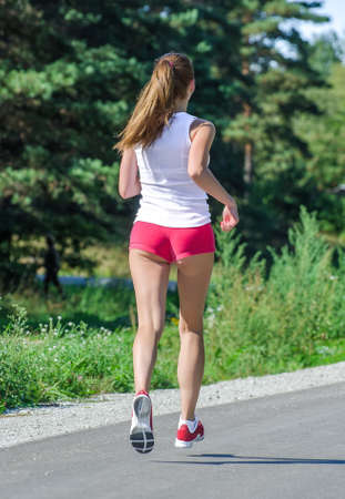 Young woman jogging in the park. Back view. photo