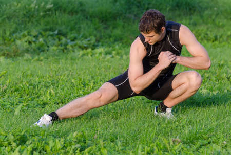 Young sportsman warming up before workout in park photo