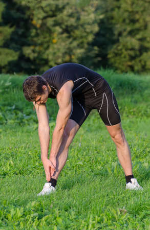 Young sportsman stretching before workout in park photo