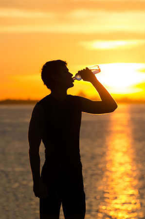 Man drinking bottle of water on the beach at sunrise photo