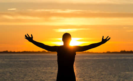 cielos abiertos: Hombre con los brazos abiertos en la playa al amanecer Foto de archivo