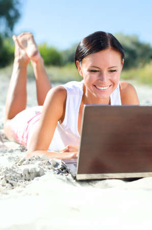 Attraente donna con laptop sdraiato sulla spiaggia