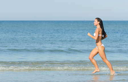 Sensual brunette running on the beach. Place for text. photo